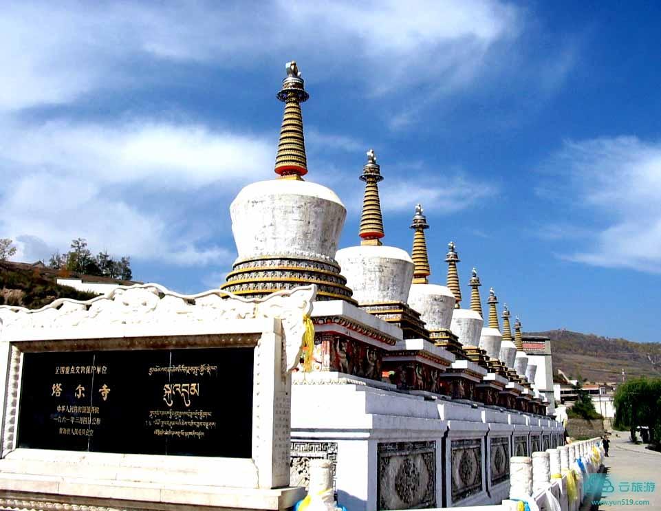 """大金瓦殿 大金瓦殿,位于全寺正中。藏语称为赛尔顿庆莫,即金瓦的意思。其建筑面积为450平方米。大金瓦殿初建于公元1560年,后于公元1711年,用黄金1300两,白银一万多两改屋顶为金顶,形成了三层重檐歇山式金顶,后来又在檐口上下装饰了镀金云头、滴水莲瓣。飞脊装有宝塔及一对火焰掌。四角设有金刚 套兽和铜铃。底层为硫璃砖墙壁,二层是边麻墙藏窗,突出金色梵文宝镜,正面柱廊用藏毯包裹,殿内还悬挂着乾隆皇帝御赐的金匾,匾额题字为""""梵教法幢""""。进入大金瓦殿内,迎面矗立着12."""
